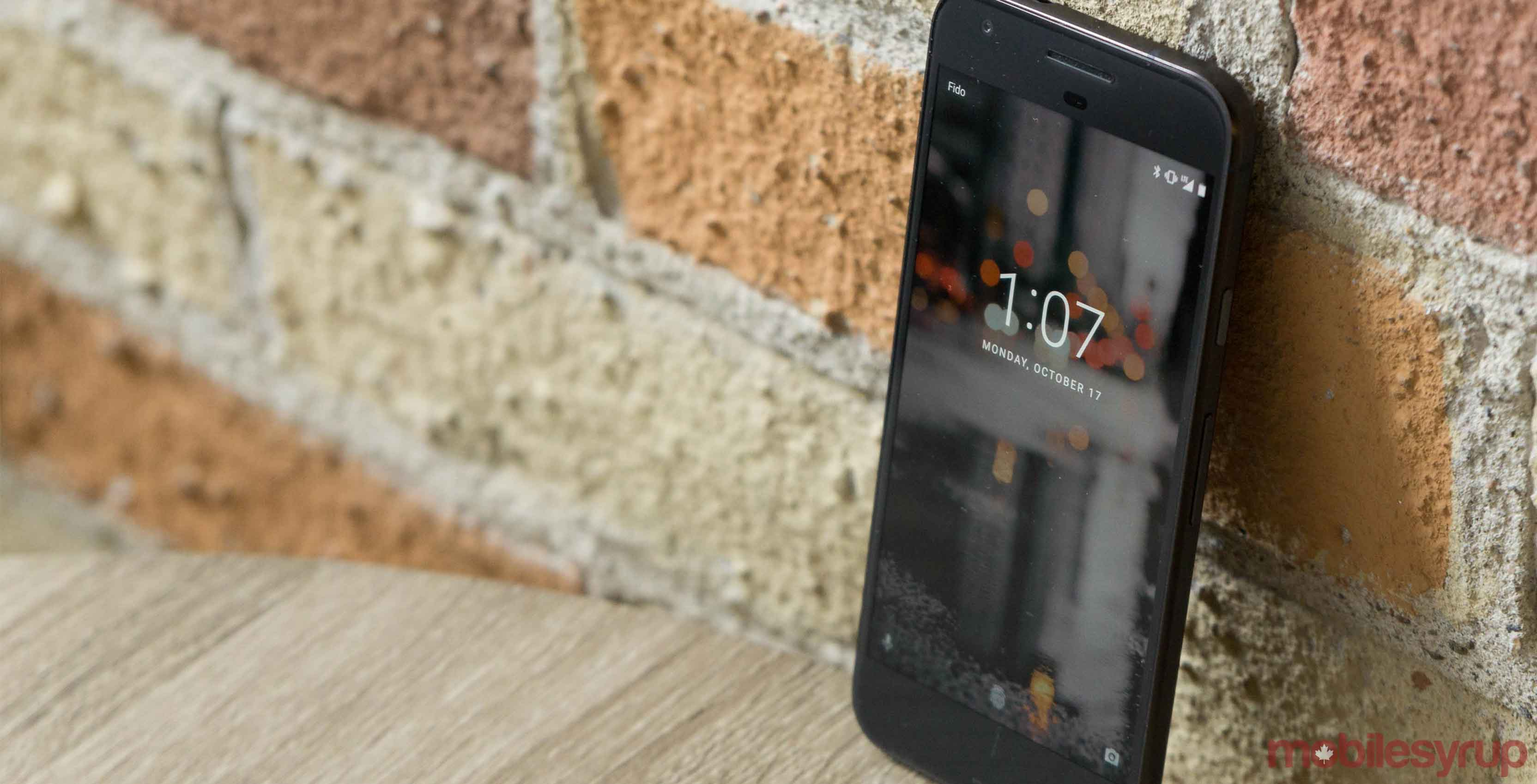 Google's Pixel smartphone leaning against a brick wall