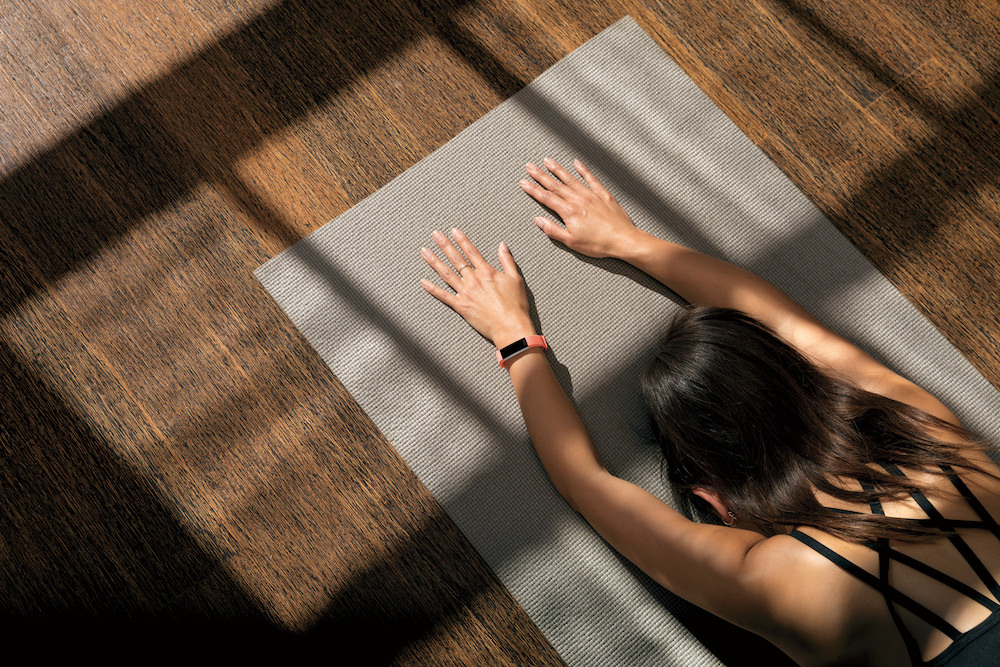 Woman practising yoga with Fitbit Alta HR