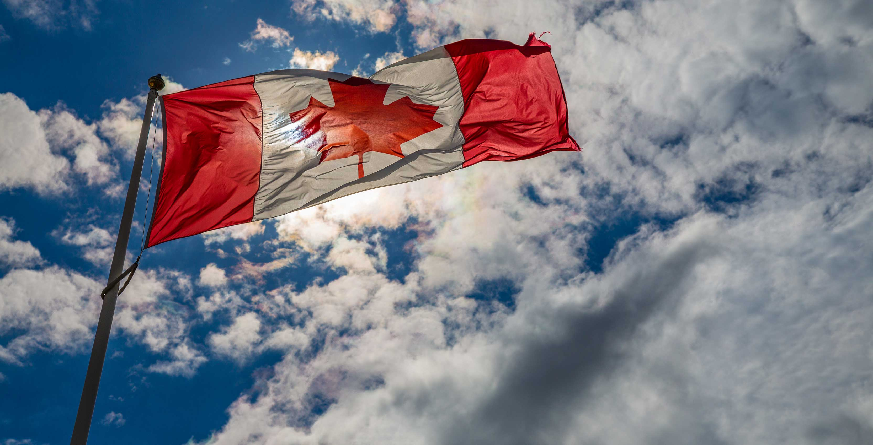 Canadian Flag with blue sky and clouds