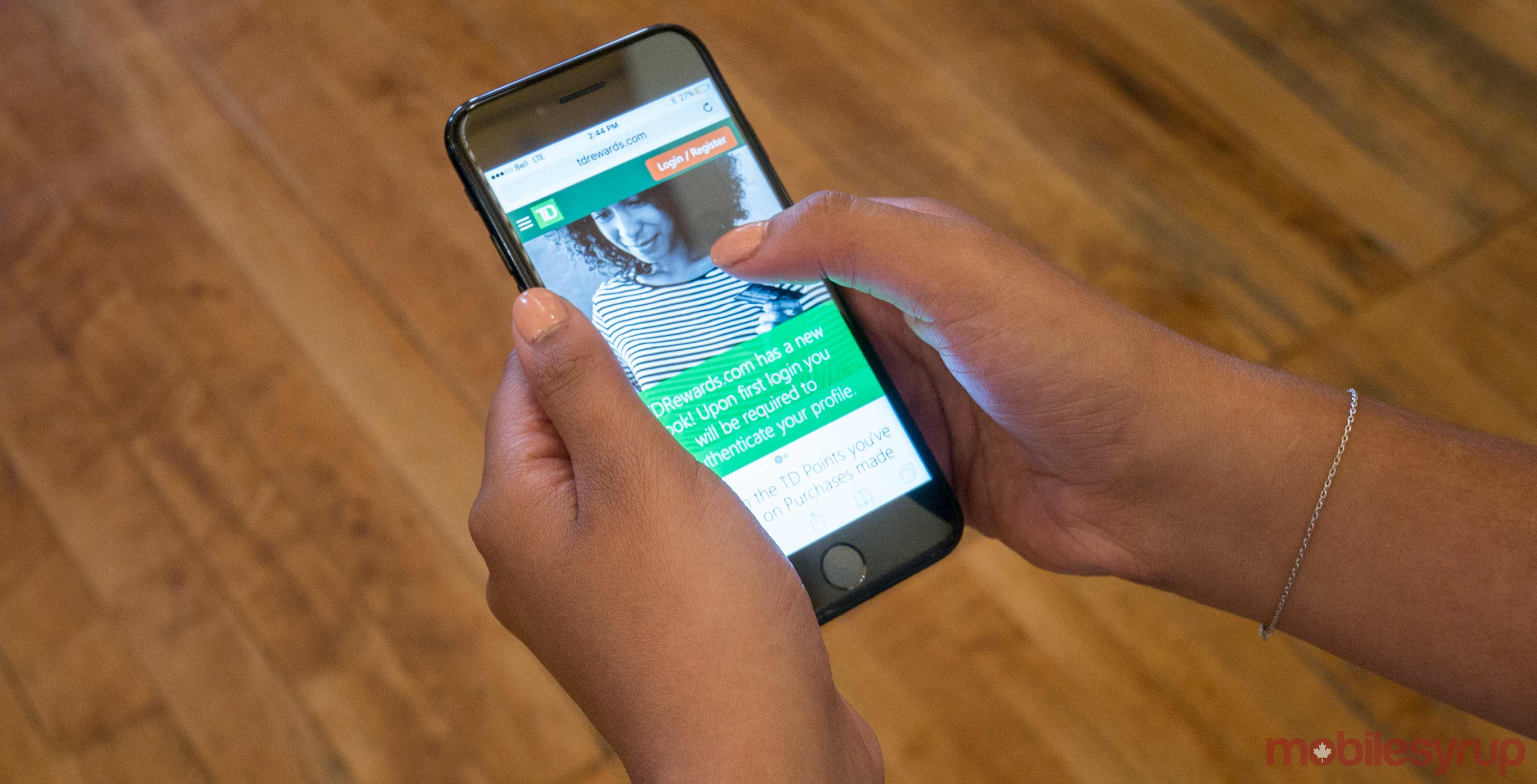 An image showing a hand holding an iPhone 7 with the TD Rewards website on-screen