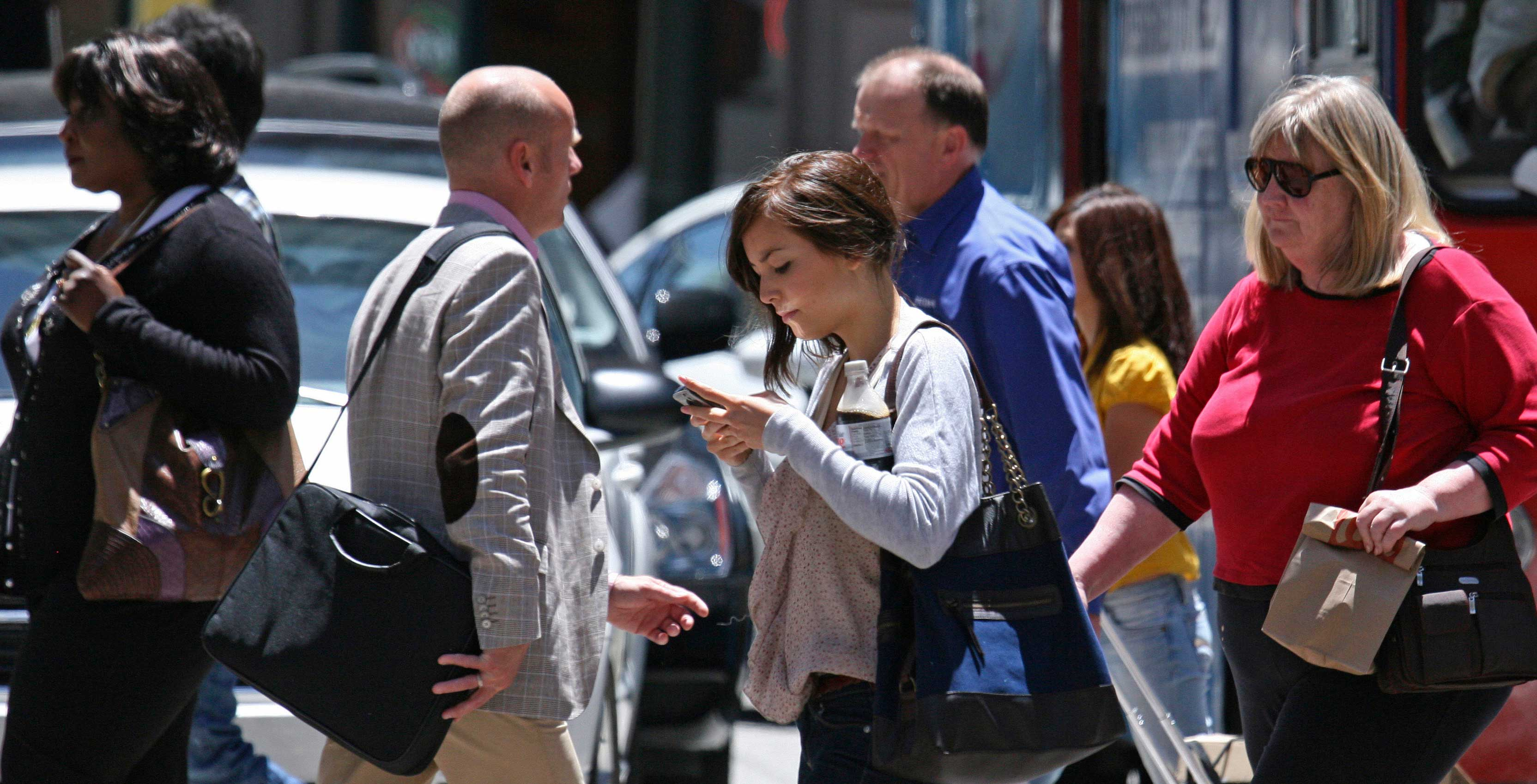 An image showing a woman looking at her phone while crossing the street