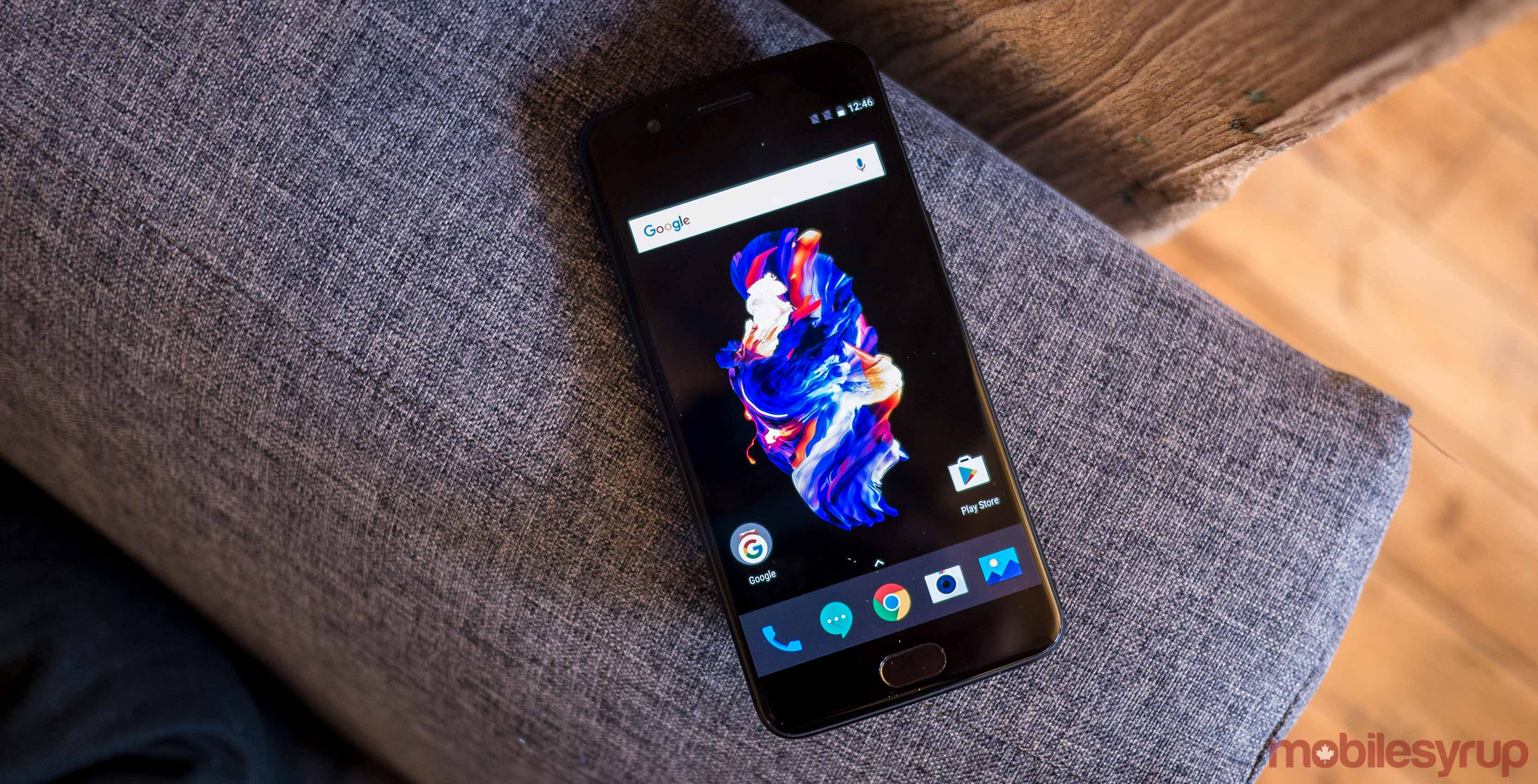 OnePlus 5 on arm of couch