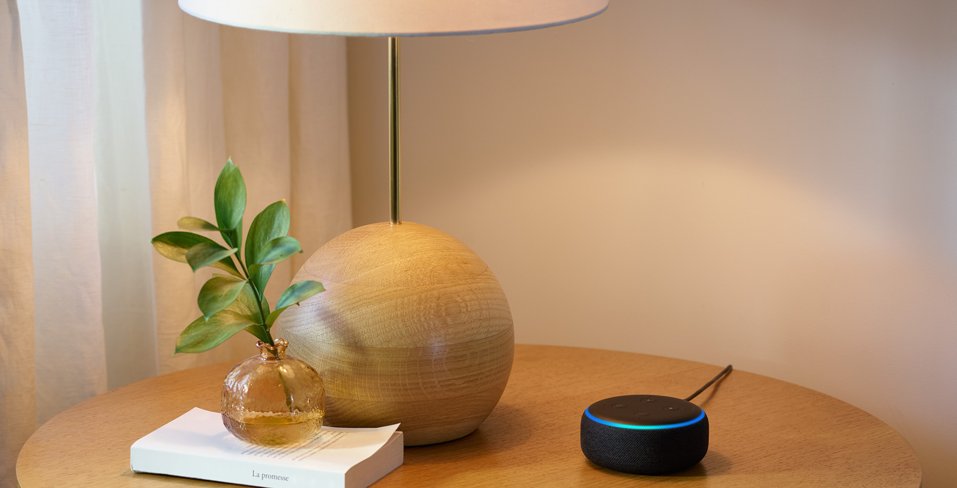 Amazon Echo on a table with a lamp