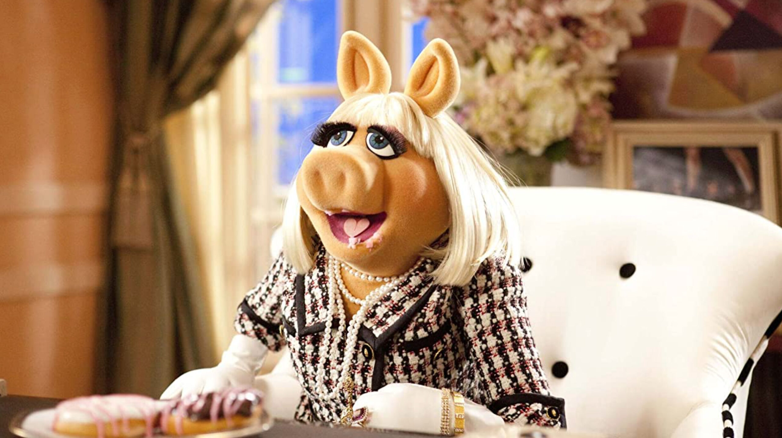 miss piggy's mouth open with donuts in her mouth. She's sitting down on a white chair.