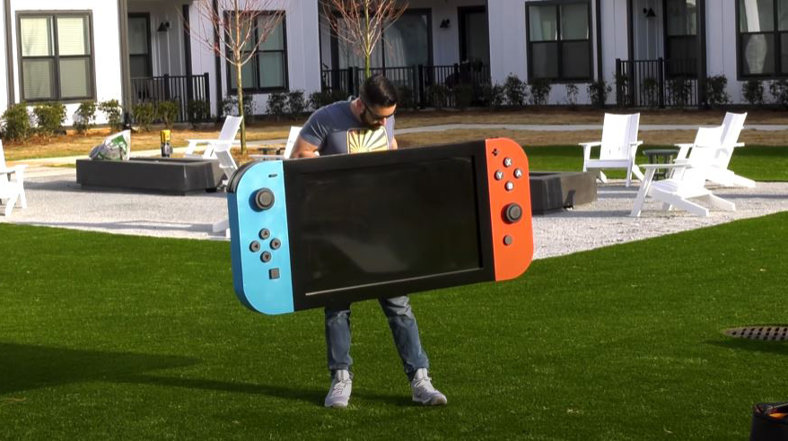 Michael Pick holding the worlds largest Nintendo Switch